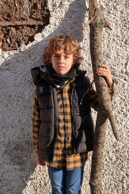 Curly cute child in touristic warm vest standing near wall and holding dry tree trunk in bright day