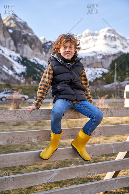 Adorable joyful kid in warm vest and yellow rubber boots sitting on old wooden fence in village at foot of snowy mountains and looking at camera