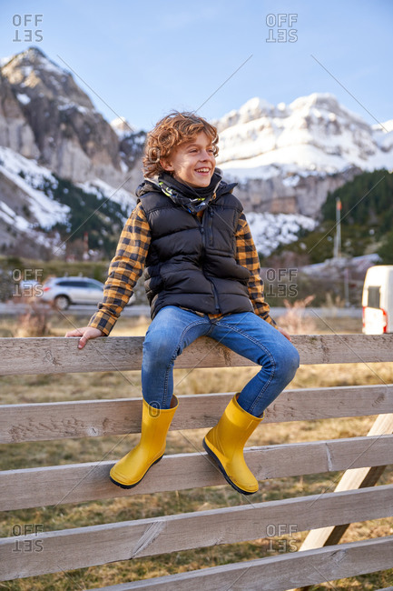 Adorable joyful kid in warm vest and yellow rubber boots sitting on old wooden fence in village at foot of snowy mountains and looking away