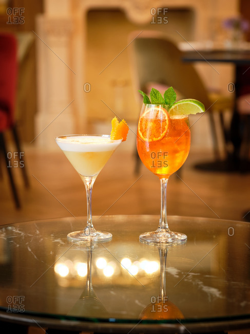 Cocktail of yellow liquid and white foam decorated with orange peel and orange cocktail with ice decorated with mint and lime on glasses table