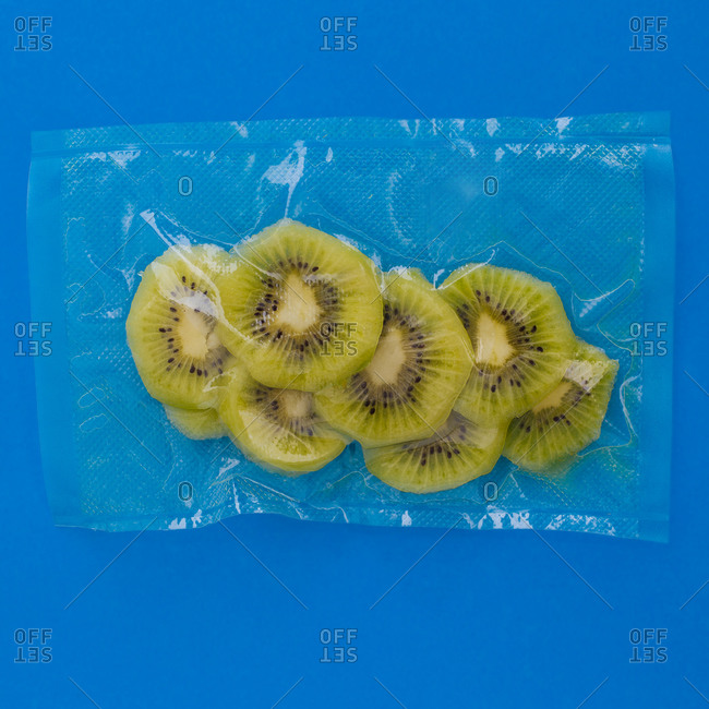 Top view of ripe green peeled kiwi in vacuum plastic bag on blue background