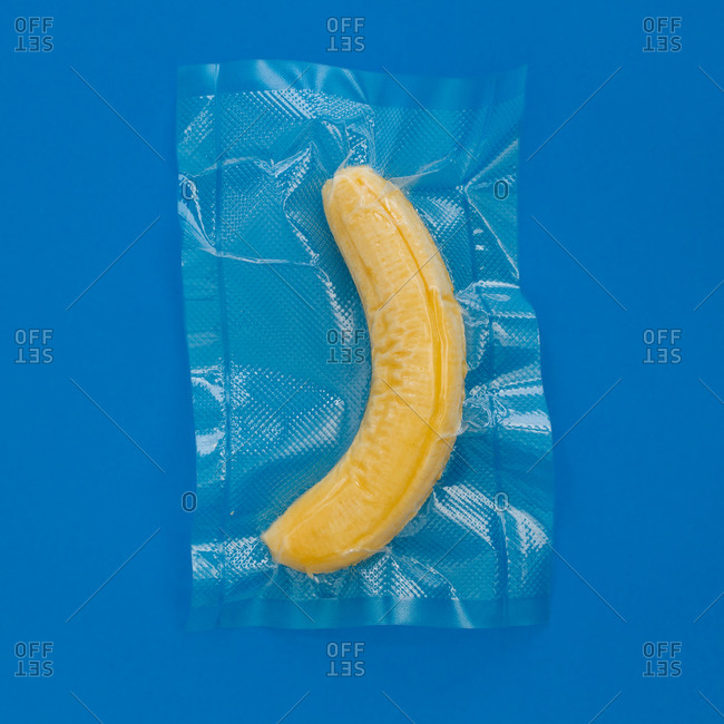 Top view of ripe yellow peeled banana in vacuum plastic bag on blue background