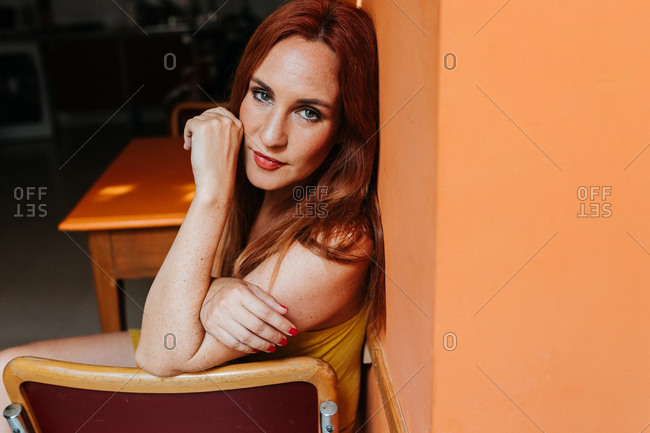 Side view from above of redhead content woman laughing and looking at camera while resting on chair in modern kitchen