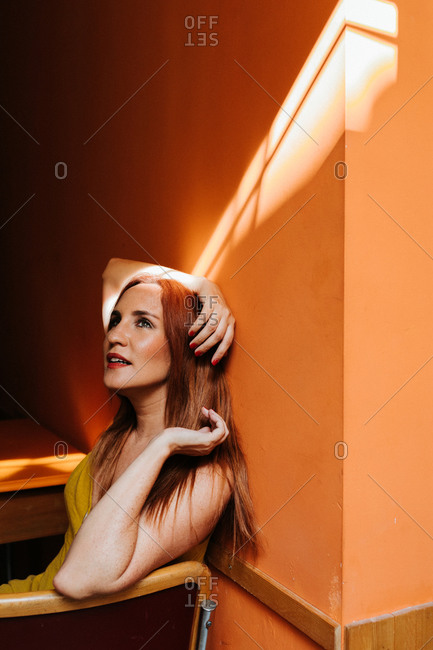 Side view from above of redhead content woman laughing and looking away while resting on chair in modern kitchen