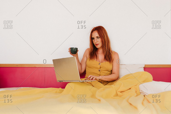 Smart redhead female freelancer in yellow gown working with laptop while drinking coffee and lying on bed
