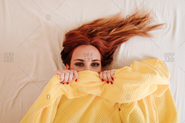 Top view of surprised redhead funny woman smiling while looking out from under yellow blanket at home