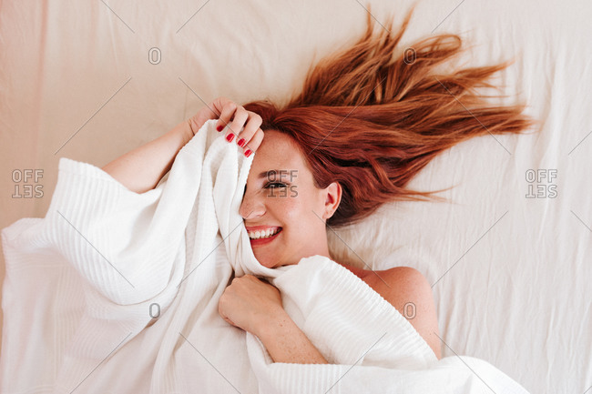 From above top view of surprised redhead funny woman smiling while looking out from under white blanket at home