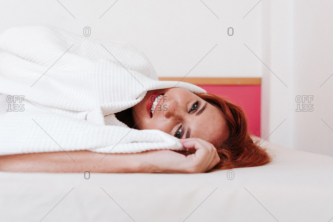 Cheerful redhead funny woman smiling while looking out from under white blanket at home