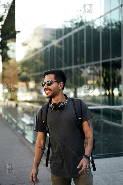 Cheerful bearded Hispanic man in casual outfit smiling and looking away with trendy sunglasses and headphones on neck at city street