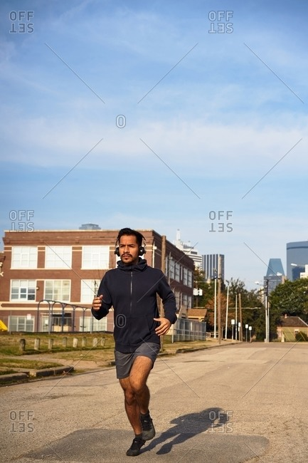Concentrated Hispanic male athlete in sports wear with headphones running along empty road at downtown