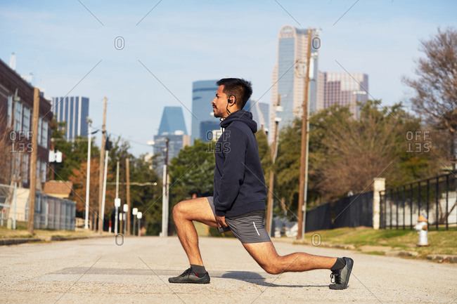 Side view hispanic male gymnast in active wear standing stretching in a park in downtown Dallas, USA