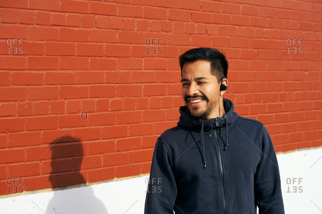 Content Hispanic man in casual wear smiling while enjoying music looking away using earphones at city street in Dallas, Texas