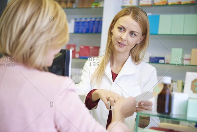 Portrait of pharmacist advising woman in pharmacy