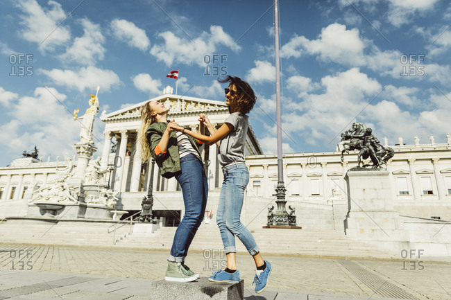 Austria- Vienna- two young women having fun in front of the parliament building