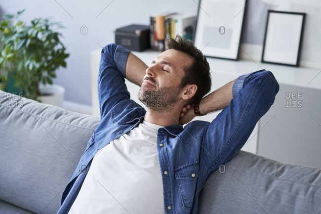 Smiling relaxed man sitting on sofa daydreaming