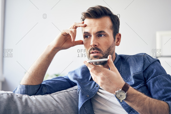 Worried man sitting on sofa using cell phone