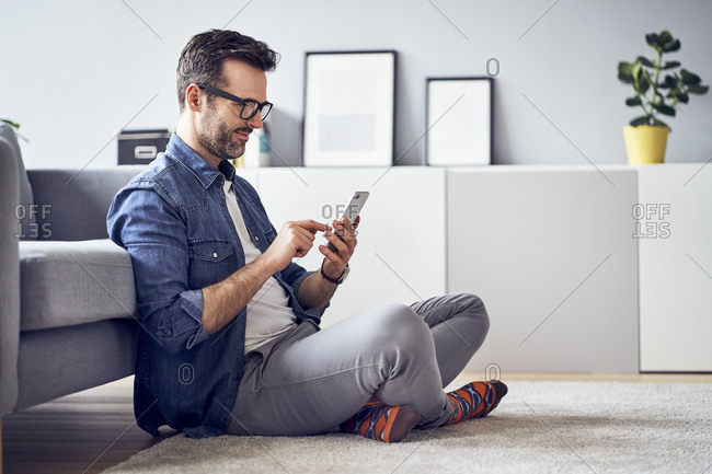 Smiling man sitting on floor in living room using cell phone