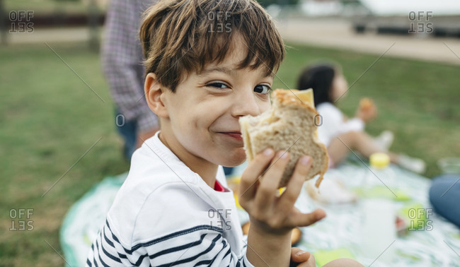 Portrait of smiling boy holding sandwich with his family in background