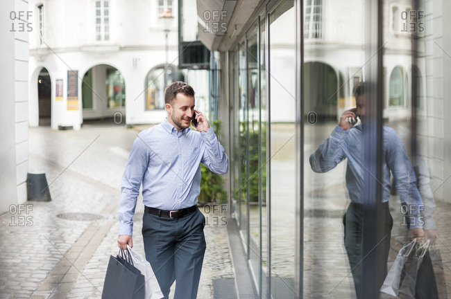 Young man with shopping bags on the phone passing a shop