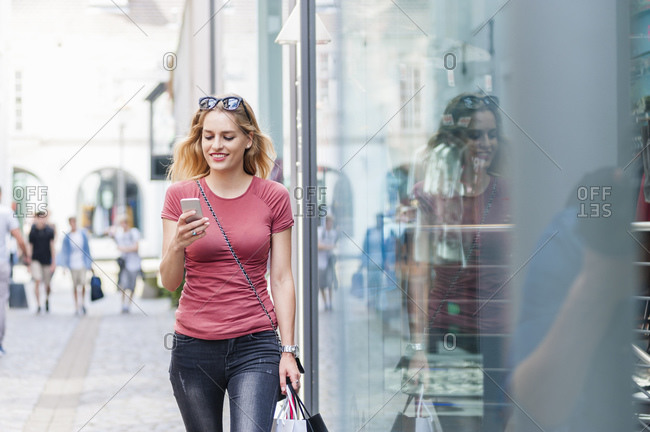 Smiling woman walking on the street with shopping bags looking at her smartphone