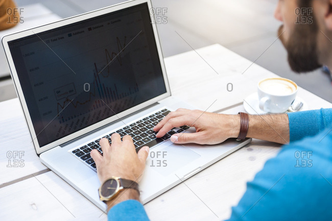 Close-up of businessman analyzing data on laptop display