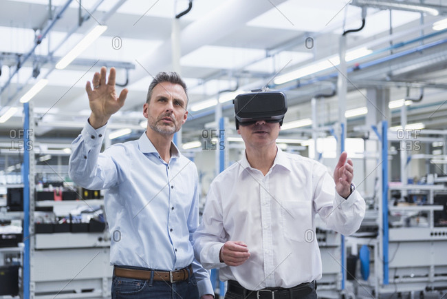 Two managers standing in company- using VR goggles