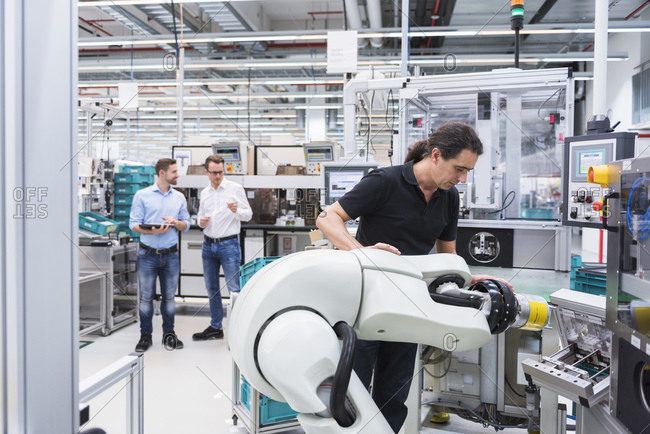 Man operating assembly robot in factory with two men in background supervising