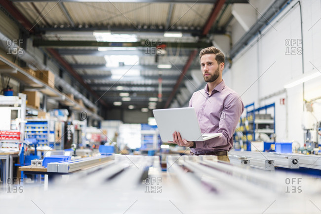 Young businessman using laptop in production hall