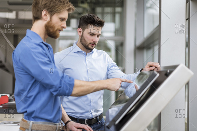Two businessmen in company using touchscreen