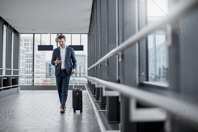 Young businessman in a passageway with cell phone- earbuds and rolling suitcase on the go