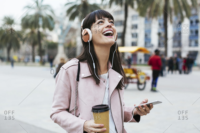 Spain- Barcelona- laughing woman with coffee- cell phone and headphones in the city