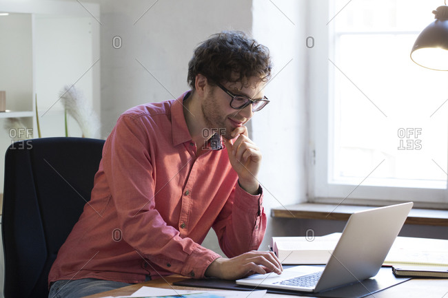 Man using laptop at desk in office