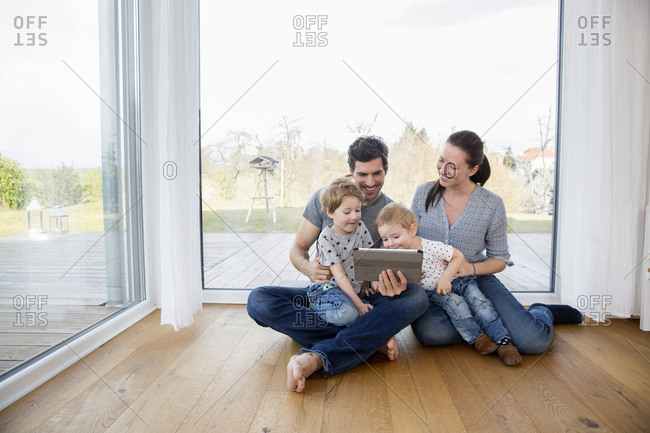 Happy family sitting on floor- using digital tablet