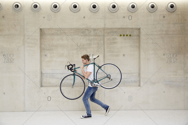 Young man carrying bicycle on his shoulder in front of concrete wall