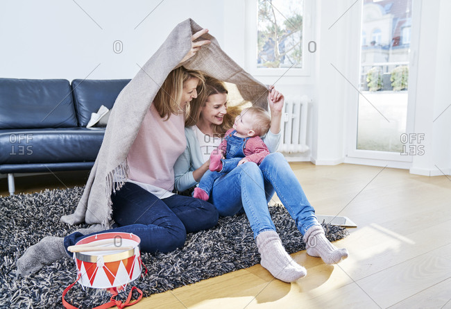 Grandmother- mother and baby girl playing in living room