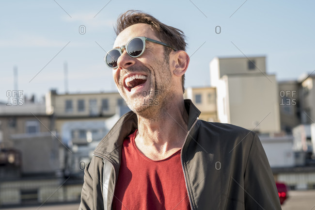 Portrait of laughing mature man with stubble wearing sunglasses