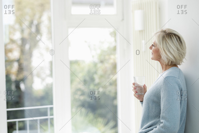 Smiling senior woman with glass of water looking out of window