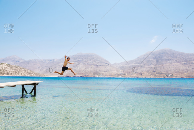 Greece- Cyclades islands- Amorgos- Aegean Sea- naked man jumping from a wooden jetty