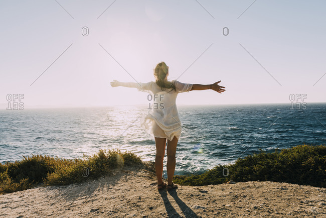 Greece- Cyclades- Naxos- woman with raised arms standing at the sea at sunset