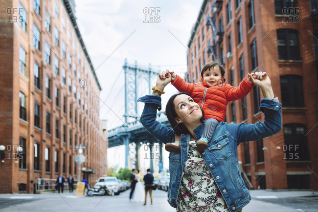 USA- New York- New York City- Mother and baby in Brooklyn with Manhattan Bridge in the background