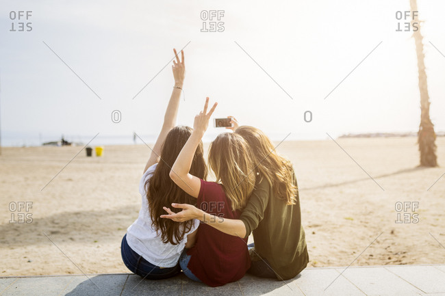 Rear view of three female friends sitting at the beach taking a selfie