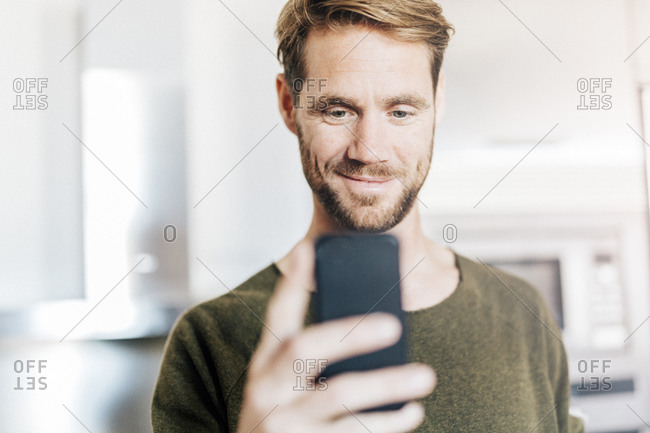 Portrait of smiling man looking at cell phone