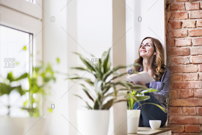 Woman sitting at home on the window sill- reading a book