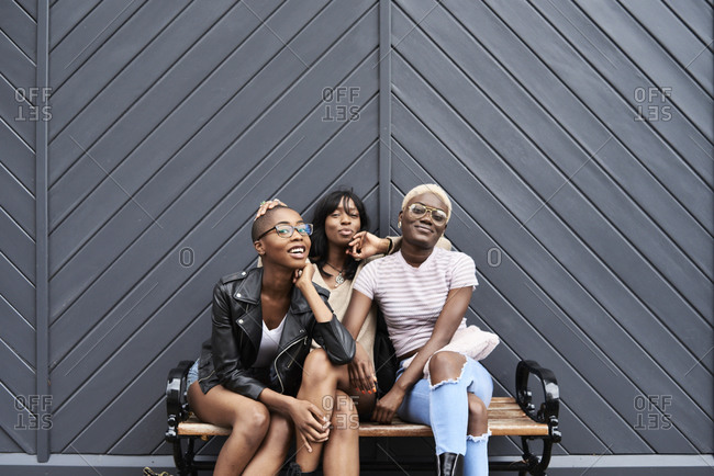 Three friends sitting together on a bench