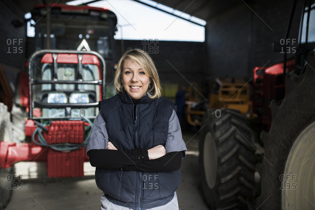 Woman standing with arms crossed in front of tractor in farm garage