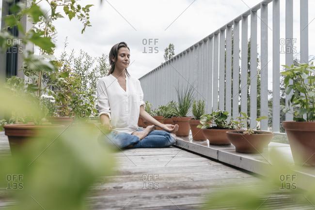 Woman sitting on balcony practicing yoga