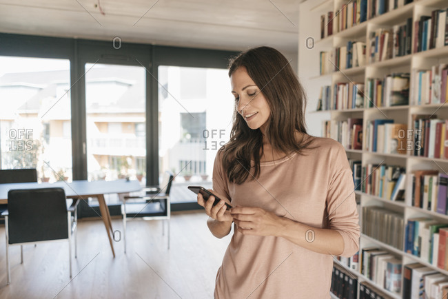 Smiling woman looking at cell phone at home