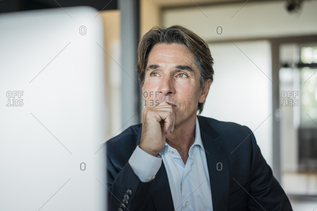 Portrait of businessman in office thinking