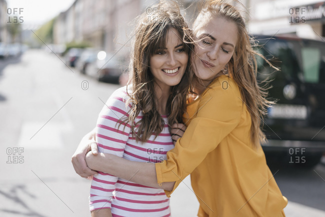 Two girlfriends embracing in the city