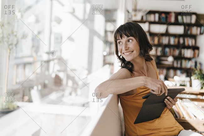 Woman sitting in cafe- using tablet pc